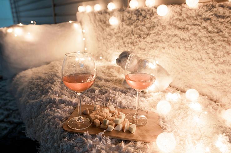 Deux verres de rosé et une planche de fromages dans un décor romantique